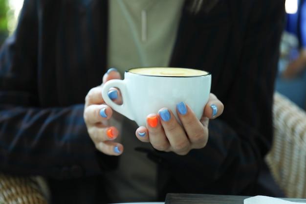 Femme tient une tasse de café délicieux, gros plan