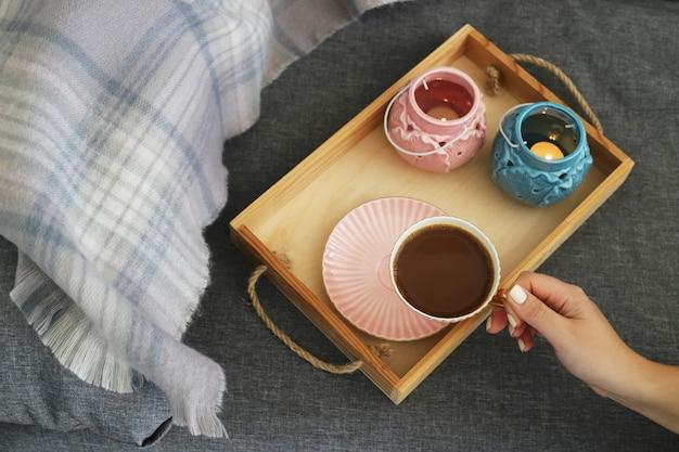 Une femme tient une tasse de café et du lait sur un plateau en bois