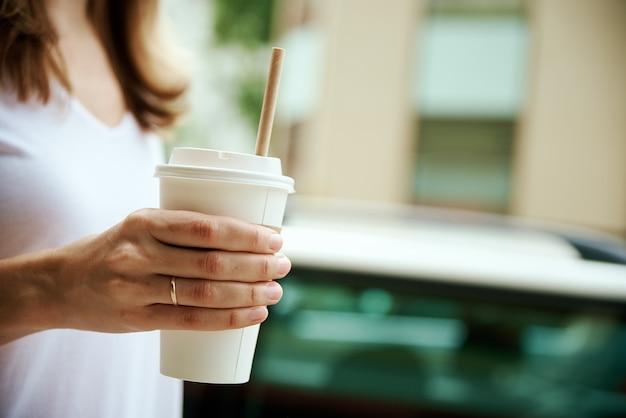 La femme tient la tasse de café de papier à la rue de ville
