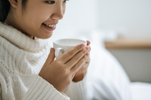 Une femme tient une tasse de café.