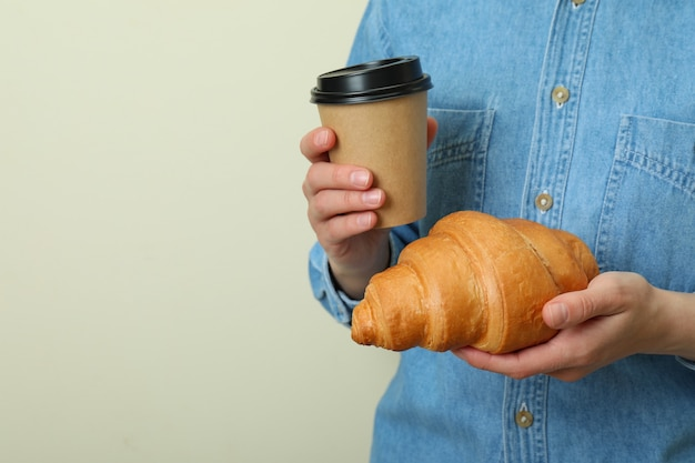 Femme tient une tasse en papier et un croissant sur beige