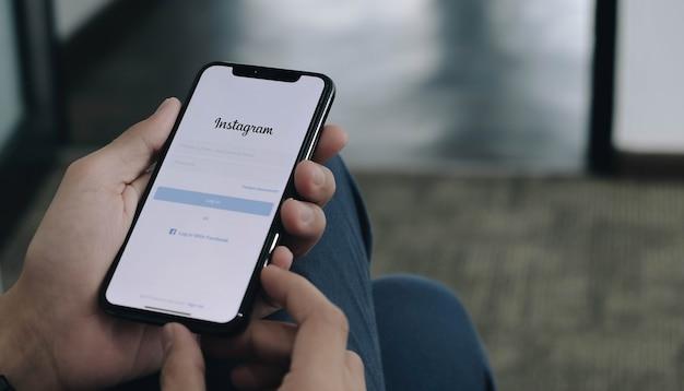 Une femme tient un téléphone avec une connexion à l'application instagram à l'écran