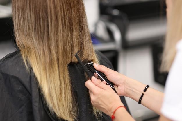 Femme tient la tondeuse à cheveux dans ses mains