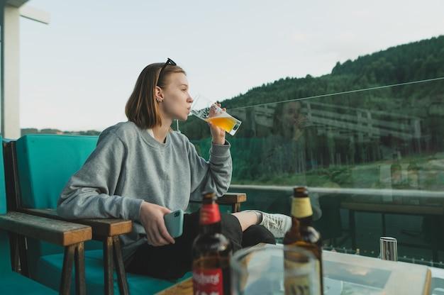 Femme tient un verre de bière froide en été sur la terrasse à une table de restaurant près de la forêt de montagne