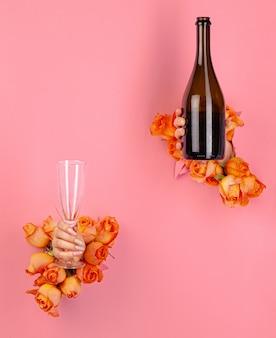 Femme, tient, a, verre champagne, dans, elle, main, mis travers, a, trou, dans, papier rose, à, roses fraîches