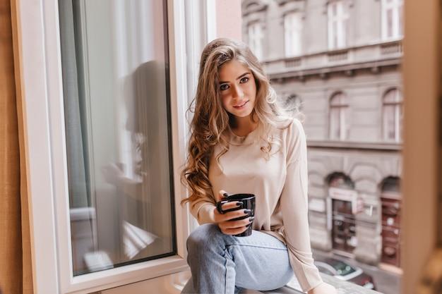 Femme timide en jeans assis sur le rebord de la fenêtre et posant avec intérêt