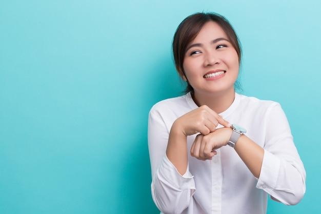 Une femme timide regarde sa montre, elle est en retard