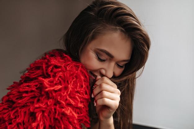 Femme timide en tenue de laine rouge vif souriant, couvrant sa bouche sur fond blanc.