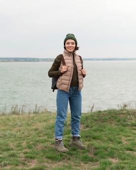 Femme de tir complet posant près de l'eau