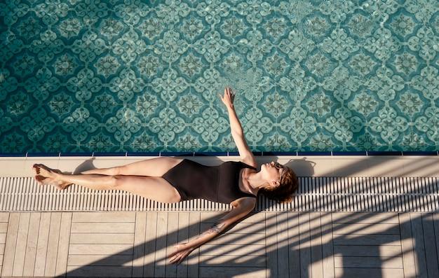 Femme de tir complet pose près de la piscine