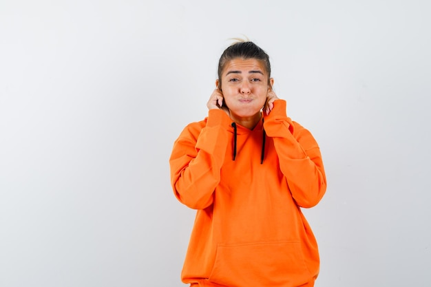 Femme tirant vers le bas ses lobes d'oreilles en sweat à capuche orange et à la drôle