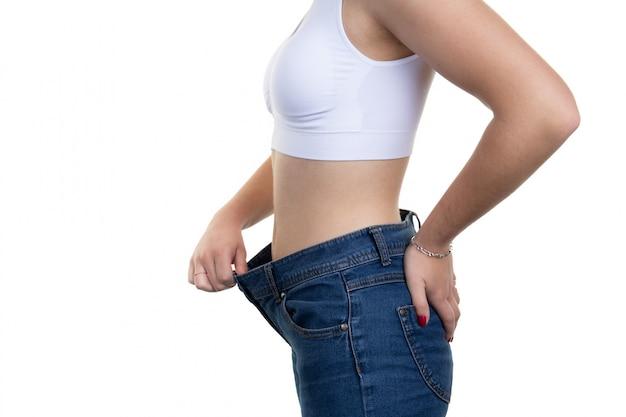 Une femme tire la taille d'un pantalon pour montrer le poids qu'elle a perdu