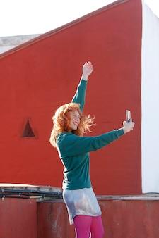Femme sur le toit prenant un selfie heureux