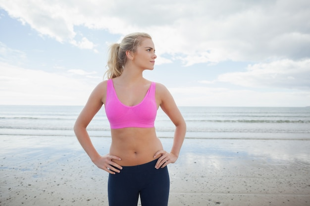 Femme tonique avec les mains sur les hanches sur la plage