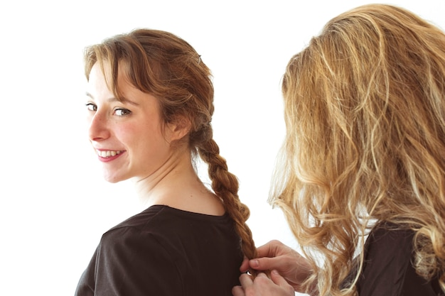 Femme tordant les cheveux tressés de sa soeur souriante contre la toile de fond blanche