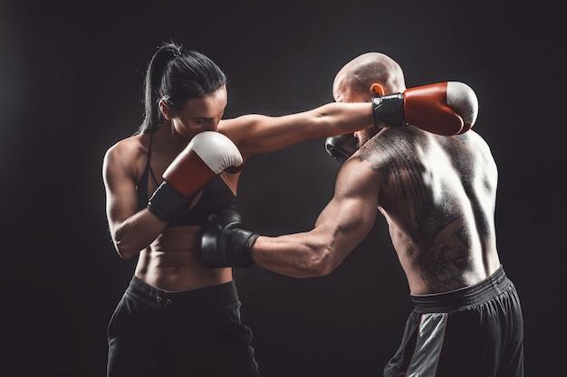 Femme torse nu exerçant avec un entraîneur à la leçon de boxe et d'autodéfense lutte féminine et masculine