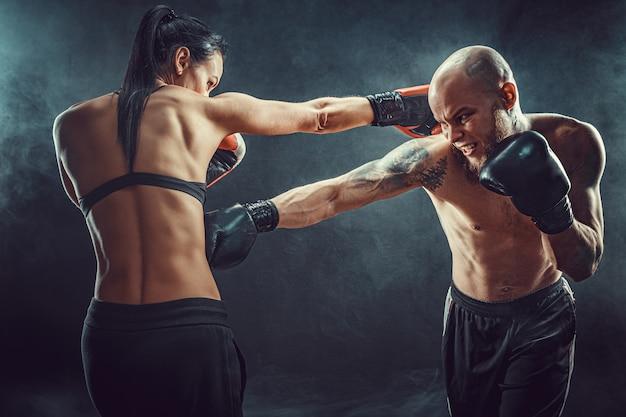 Femme torse nu exerçant avec un entraîneur à la leçon de boxe et d'autodéfense, studio, fond sombre. combat féminin et masculin.