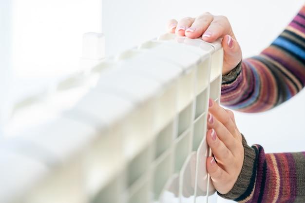Femme touchant le radiateur chaud avec les deux mains