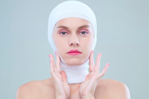 Femme touchant le visage après la chirurgie