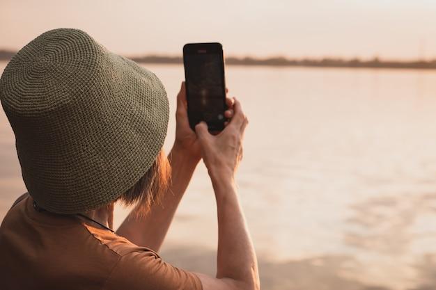 Femme de tourisme au chapeau sur la plage photographiant au téléphone la mer et le coucher du soleil