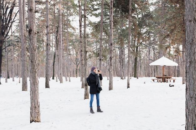 Femme de tourisme avec binoculaire debout dans la forêt d'hiver