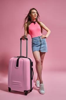 Femme de tourisme dans des vêtements décontractés d'été tenant une valise sur fond rose