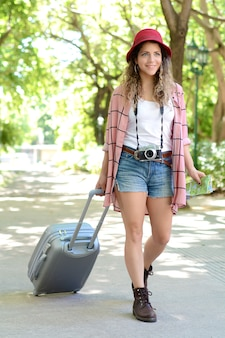 Femme de tourisme portant une valise dans la rue