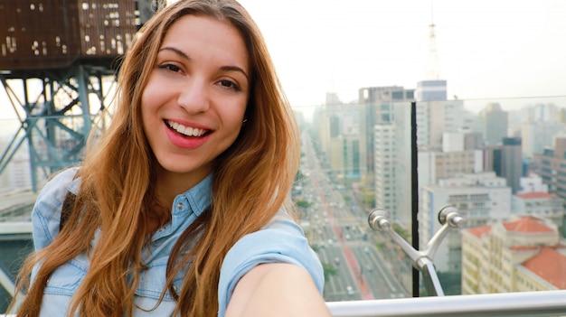 Femme de tourisme prenant selfie photo à l'horizon de sao paulo. heureuse belle fille prendre autoportrait de gratte-ciel et de l'avenue paulista à sao paulo