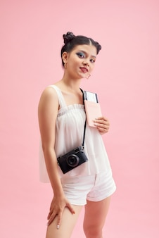 Femme de tourisme en vêtements décontractés d'été. femme souriante asiatique. passager voyageant à l'étranger pour voyager sur fond rose