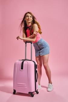 Femme de tourisme en vêtements décontractés d'été sur fond rose tenant une carte de crédit