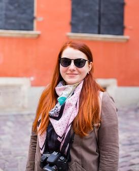 Femme de tourisme de voyage avec appareil photo, fille rousse de style à lunettes de soleil
