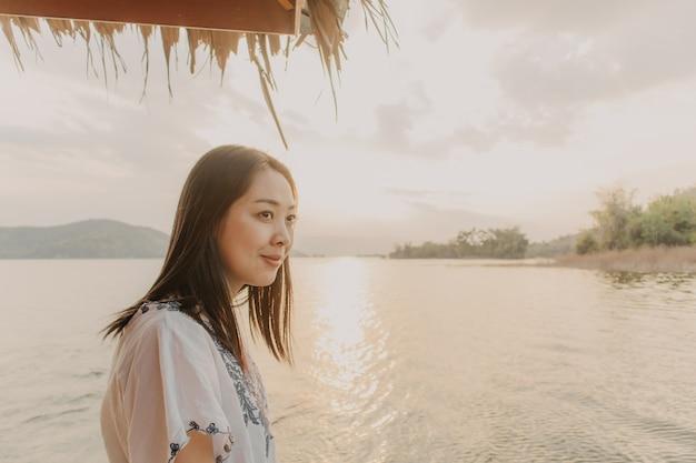Femme touriste admire la belle nature du lac avec un ciel de coucher de soleil chaud.