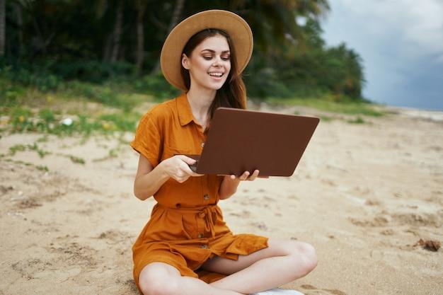 Femme touriste assis sur la plage en face de l'ordinateur portable communiquant l'air frais de l'île nature artiste indépendant exotique