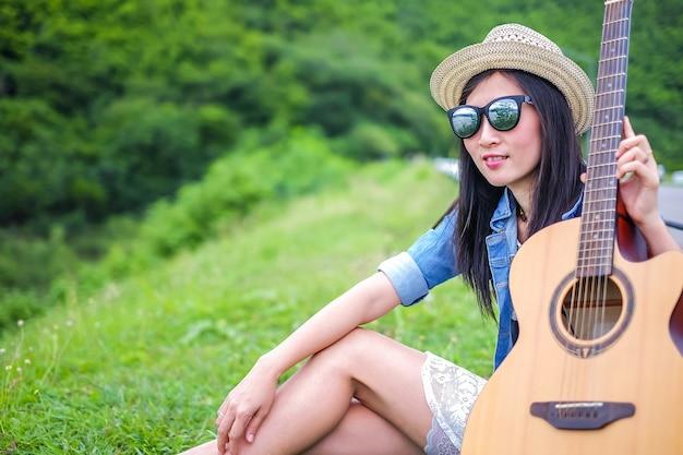 Femme touriste assis sur le verre à côté de la route et en prenant une guitare