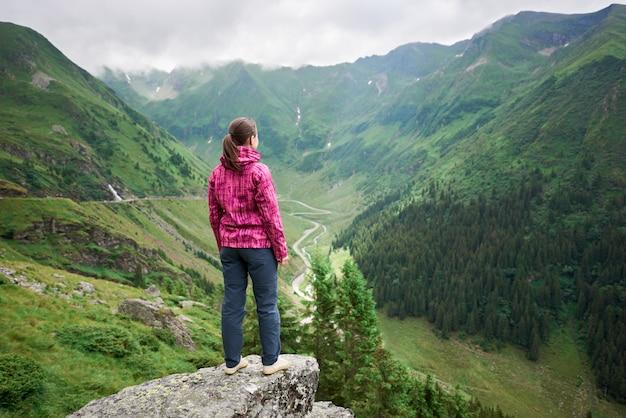 Femme touriste bénéficie de beaux paysages de la vallée de montagnes verdoyantes, roumanie