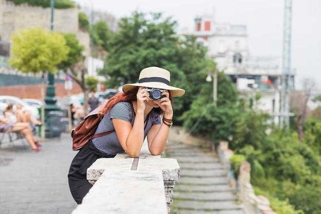 Femme touriste avec caméra sur balcon