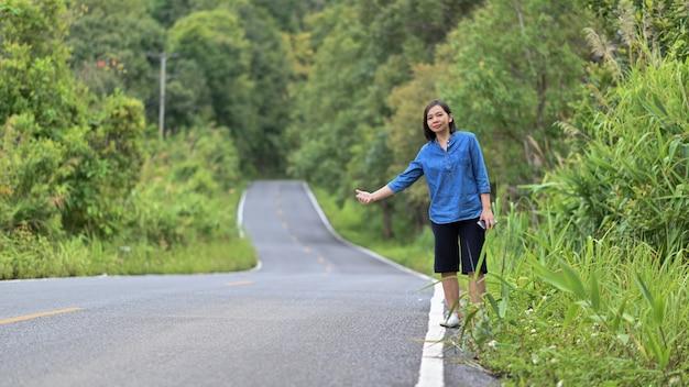 Femme touriste debout auto-stoppeur pour voyager.