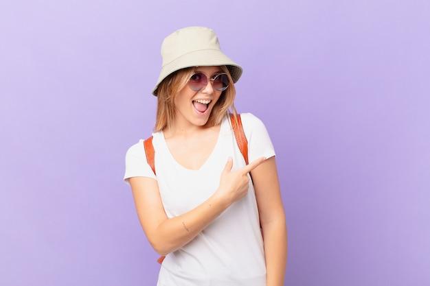 Femme de touriste jeune voyageur à la recherche excitée et surprise en pointant vers le côté