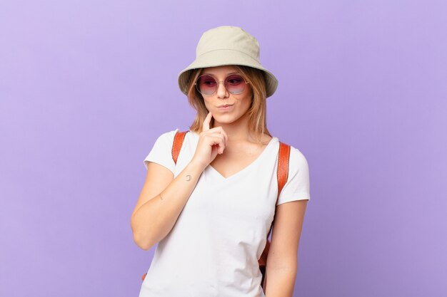 Femme de touriste jeune voyageur se sentant perplexe et confus se gratter la tête