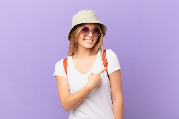 Femme de touriste jeune voyageur souriant joyeusement se sentir heureux et pointant vers le côté