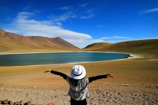 Femme touriste levant les bras en admirant l'incroyable lagon bleu laguna miniques, chili