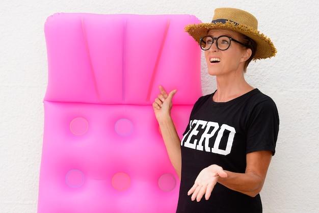 Femme de touriste nerd mature tenant un matelas pneumatique alors qu'elle a l'air inquiète