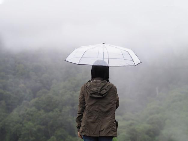 Femme touriste avec parapluie sur fond de forêt tropicale verte.