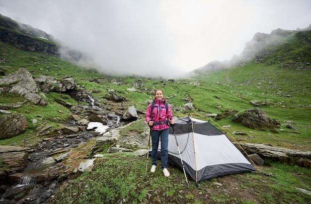Femme touriste près de la tente dans la vallée des montagnes roumaines