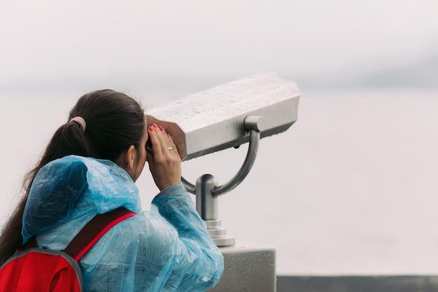 Femme touriste à la recherche à travers des jumelles à pièces avec vue sur la mer