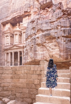 Femme touriste en robe de couleur et chapeau profitant du trésor, al khazneh dans l'ancienne ville de petra, jordanie