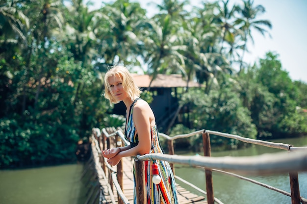 Une femme touriste en robe lumineuse par une journée tropicale ensoleillée. jeune belle fille se dresse sur un pont en bois sur une petite rivière contre la jungle de palmiers floue. paysage pittoresque avec espace copie.