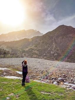 Femme touriste avec un sac à dos, admirant les montagnes, marchant dans les montagnes en su