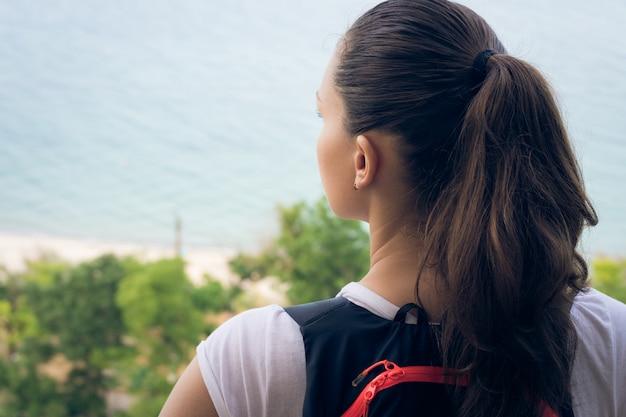 Femme touriste se dresse au sommet d'une colline sur la plage et regarde au loin