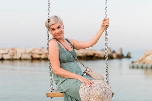 Femme de touriste senior smiley à la plage en balançoire